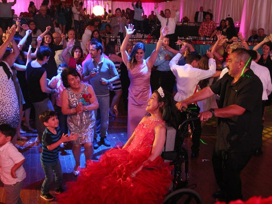 Friends and family dance with Karizma Vargas during her quinceañera celebration.