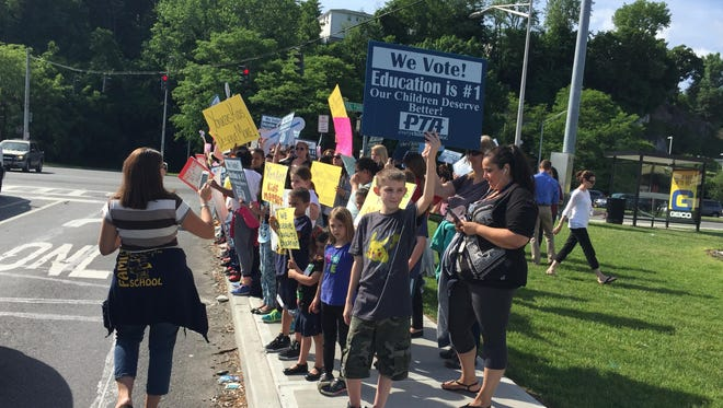 Parents and students from three Yonkers schools waved signs and chanted on the side of Central Park Avenue June 3 to protest cuts to programs. The state Legislature voted Thursday to provide additional funding.