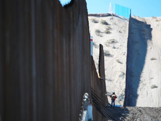 A worker is dwarfed by the border fence which is under