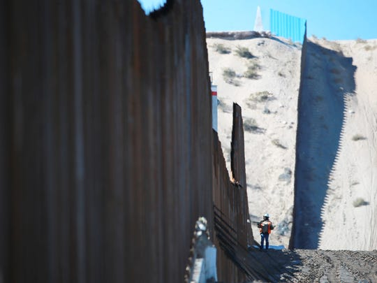 A worker is dwarfed by the border fence which is under construction in Sunland Park, N.M. across from Anapra, Mexico. The monument which marks the border between the U.S. and Mexico is at top center of photo.