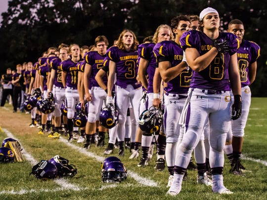 Oconomowoc lines up for the national anthem prior to the Homecoming game against Wisconsin Lutheran on Friday, Sept. 27, 2013.