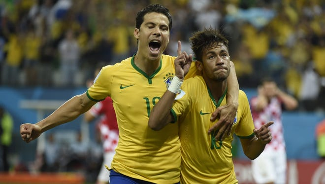 Brazil's forward Neymar (R) celebrates with his teammate Brazil's midfielder Hernanes after scoring a penalty during a Group A football match between Brazil and Croatia at the Corinthians Arena in Sao Paulo during the 2014 FIFA World Cup on June 12, 2014.  AFP PHOTO / ODD ANDERSENODD ANDERSEN/AFP/Getty Images