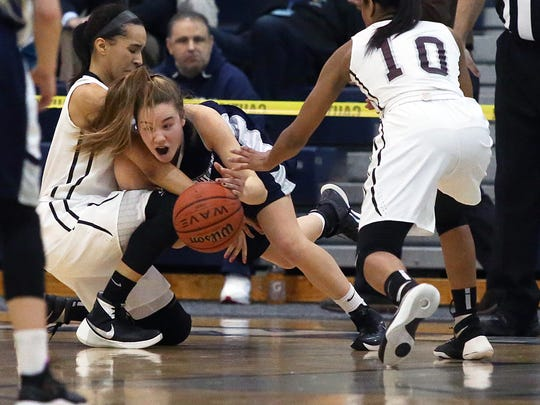 Rutgers Prep takes on Manasquan in the 2016 Girls Tournament of Champions basketball game at the Pine Belt Arena in Toms River on Friday March 18, 2016. Manasquan's # 5 (center)- Addie Masonius tries to get past the tight defense of Rutger Prep's # 4 Chiara Tibbitt (left) and # 10 Jahsyni Knight (right)