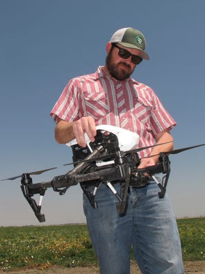 Danny Royer, vice president of technology at Bowles Farming Co., prepares to pilot a drone over a tomato field near Los Banos, Calif.