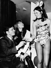 Hugh Hefner (left) and then-girlfriend Barbi Benton (center) are served by Playboy Club bunny model upon their arrival at LaGuardia Airport in New York.