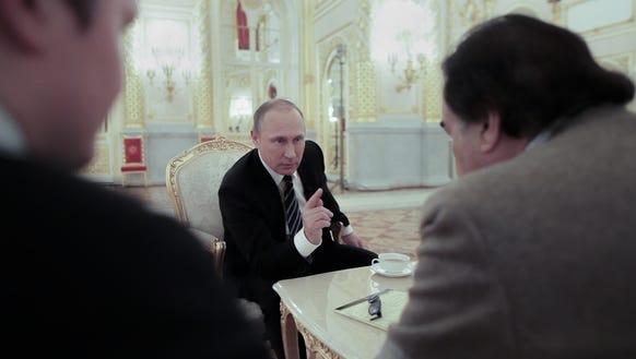 Filmmaker Oliver Stone, right, listens as Russian President