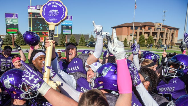 University of Sioux Falls football players hoist the key to the city in the air while celebrating their victory over their rival Augustana University at Bob Young Field in Sioux Falls on Saturday, Oct. 28, 2017.