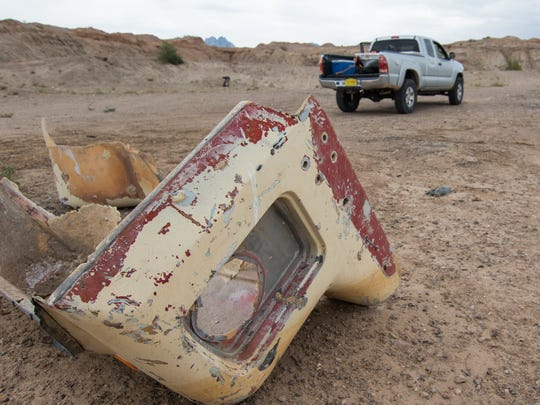 Broken and discarded truck parts litter the desert