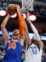 New York Knicks center Enes Kanter (00) attempts a layup as Dallas Mavericks forward Salah Mejri (50) defends during the first half of an NBA basketball game Sunday, Jan. 7, 2018, in Dallas. (AP Photo/Brandon Wade)