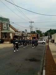 DSP Pipe and Drum team arrives on W. 9th St. for Biden