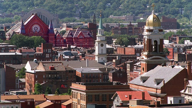 Cincinnati Music Hall, left, Old St. Mary's Church, center, and old St. Paul's Church, right, soar up over the rooftops of Over-the-Rhine.