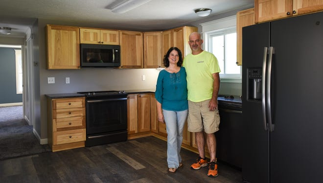 John and Trixie Tanner pose for a portrait in the newly remodeled kitchen of the home they purchased last September. They had the intention of flipping it but during renovations, they fell in love with the home and property.  They plan to sell their home in Charlotte and move to Eaton Rapids.