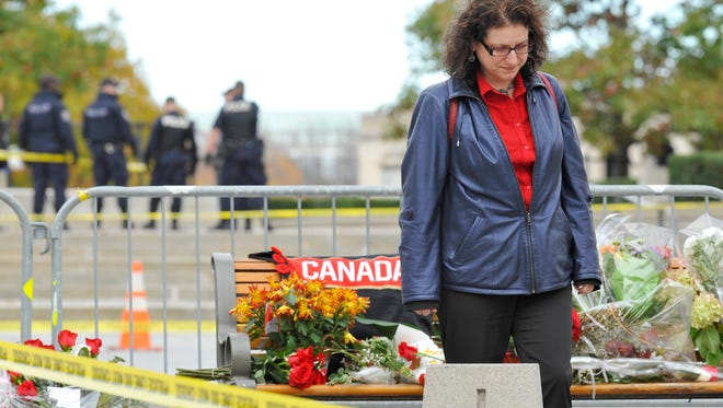 A woman walks away after placing flowers near the National War Memorial in Ottawa on Oct. 23.