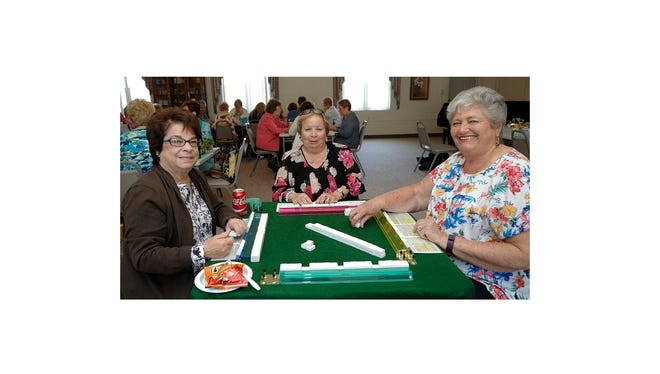 """The Millville Woman's Club recently held a game day for members to play games of their choice, including bridge, pinochle and, scrabble and other assorted games. There was also a """"conversation table"""" for non-players. (From left) Pam McNamee, president, Millville Woman's Club, Andi Manno and Janet Page enjoy a game of Mahjong."""