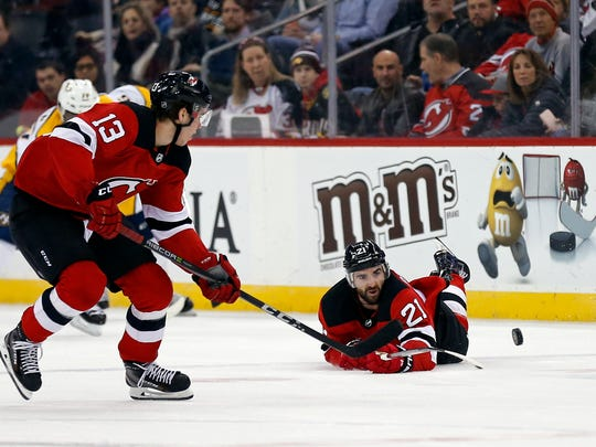 New Jersey Devils right wing Kyle Palmieri (21) passes the puck to New Jersey Devils center Nico Hischier (13) against the Nashville Predators during the first period at Prudential Center.