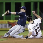 Milwaukee Brewers second baseman Scooter Gennett is unable to hang on to the throw as Miami Marlins' J.T. Realmuto steals second base during the fourth inning Wednesday in Miami.