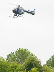 A Louisville Metro Police helicopter hovers over a densely wooded area searching for a bear that was spotted in the populated area. The location of the bear is suspected to be south of Pacer Court NW and west of Federal Drive NW in Corydon, In...18 July, 2016