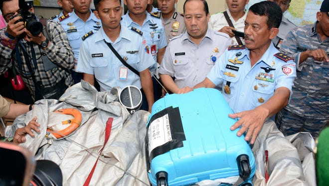 Indonesian officials shows airplane parts and a suitcase found floating on the water near the site where AirAsia Flight 8501 disappeared.