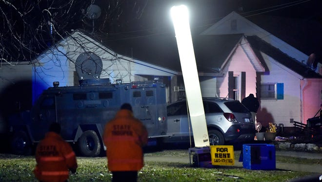 Law enforcement officials respond to the scene of a shooting where officer Christopher Ryan Morton was killed and two other officers wounded as they responded to a 911 call on Tuesday evening, March 6, 2018, in Clinton, Missouri.