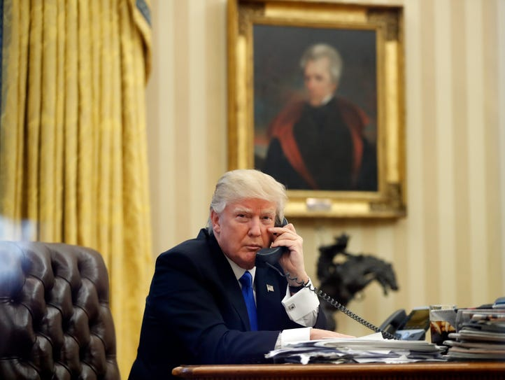 President Donald Trump speaks on the phone in the Oval