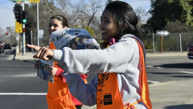 Mt. Whitney High School students Sadee Perez and Jasmine Gonzalez sell Kids Day newspapers on the corner of Mooney Boulevard and Noble Avenue in Visalia, Tuesday morning.