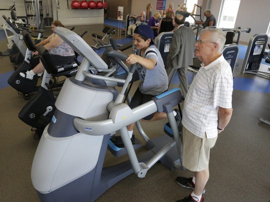 Lincoln Eichstadt, 9, tries out the new adaptive motion trainer as his grandfather Jim Eichstadt watches Thursday July 13, 2017, at the Downtown Oshkosh YMCA. The organization marked the completion of Phase 1 of a multi-phase renovation as members and guests, with an open house that included tours of the facility.