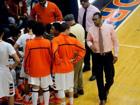 Assistant basketball coach Clovis Gallon, right, approaches