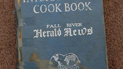 """In this undated photo a rare copy of """"The International Cookbook,"""" published by the Fall River Herald News in 1929, is seen in Fall River, Mass. Chuck Williams, owner of the Eagle Trading Company, a store solely devoted to finding and selling rare, old, out-of-print and hard-to-find cookbooks ownes a copy of this book in his private collection."""