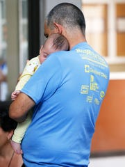 A father holds his daughter on May 11 at the Houchen Community Center as he and the rest of his family await news of a flight to another state where they planned to meet with other family members. Hundreds of Cuban immigrants have been processed at the center since the first wave of refugees entering the United States through Juárez arrived.