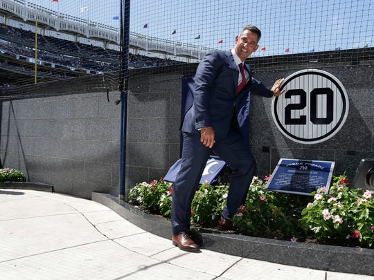 Former New York Yankees catcher Jorge Posada poses with his retired jersey number, 20, during an unveiling ceremony in Monument Park before a baseball game against the Cleveland Indians, Saturday, Aug. 22, 2015, in New York. (AP Photo/Julie Jacobson)