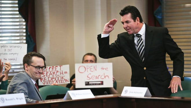 Papa John's founder John Schnatter salutes another board member before the start of the Wednesday meeting to decide Tom Jurich's fate at the University of Louisville. Oct. 18, 2017