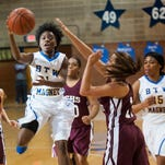 BTW Magnet's Jada Davison (1) dishes a pass over Elmore County's Hannah Traylor (15) in area tournament action at Lanier High School in Montgomery, Ala. on Saturday February 12, 2016.