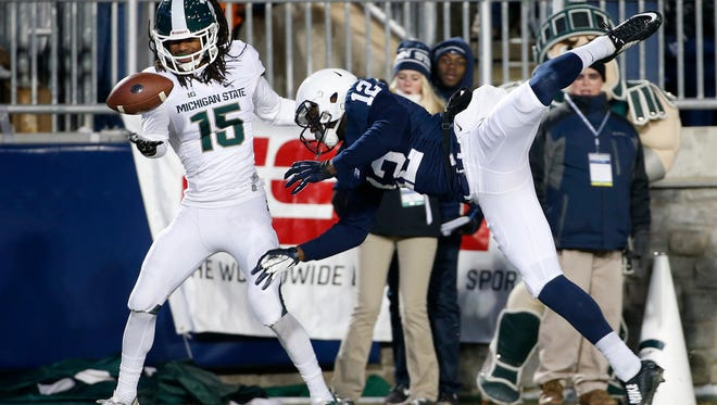 Michigan State cornerback Trae Waynes (15) intercepts a pass in the end zone intended for Penn State wide receiver Chris Godwin (12) during the second half of an NCAA college football game in State College, Pa., Saturday, Nov. 29, 2014.