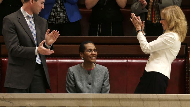 FILE- In this May 6, 2013 file photo, Justice Sheila Abdus-Salaam, center, receives applause after her confirmation to serve on the New York State Court of Appeals from Craig Alfred of Gov. Andrew Cuomo's appointments office, left, and Albany City Court Judge Rachel Kretser, in the Senate gallery at the Capitol in Albany, N.Y.