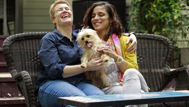 Sophy Jesty, left, and Val Tanco play with their dog, Biscuit, at their home in Knoxville, Tenn. When Tanco and Jesty began dating during post-graduate veterinary training at Cornell University, their relationship faced more than the usual run of hurdles. Tanco is Argentinian, and once her residency ended, she wound up on the west coast of Canada, while Jesty remained on the east coast of the U.S. The two wed legally in New York a year later in a brief courthouse ceremony. In the meantime, both had been offered jobs at the University of Tennessee College of Veterinary Medicine, in Knoxville. They accepted, but only after they got to Tennessee did the ramifications of living in a state that didn't recognize their marriage become apparent.