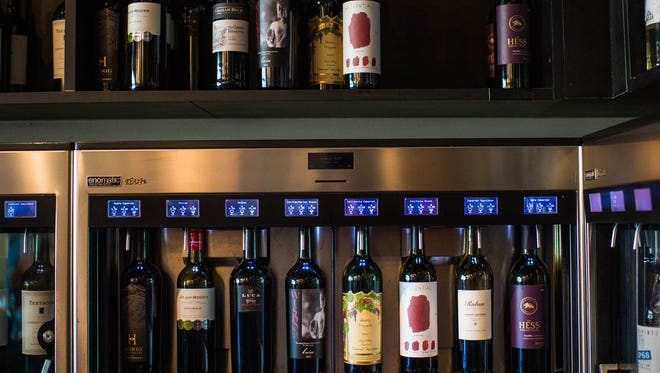 Bottles of wine in dispensers are displayed at Pour wine bar in Lafayette, La., Tuesday, Oct. 13, 2015. Customers purchase a card with monetary value and swipe their cards to dispense wines from the machines.