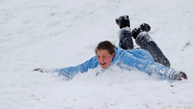 In this Thursday, Dec. 25, 2014 photo, Lillian England, 13, sleds down an embankment on the College of Southern Idaho campus in Twin Falls, Idaho.