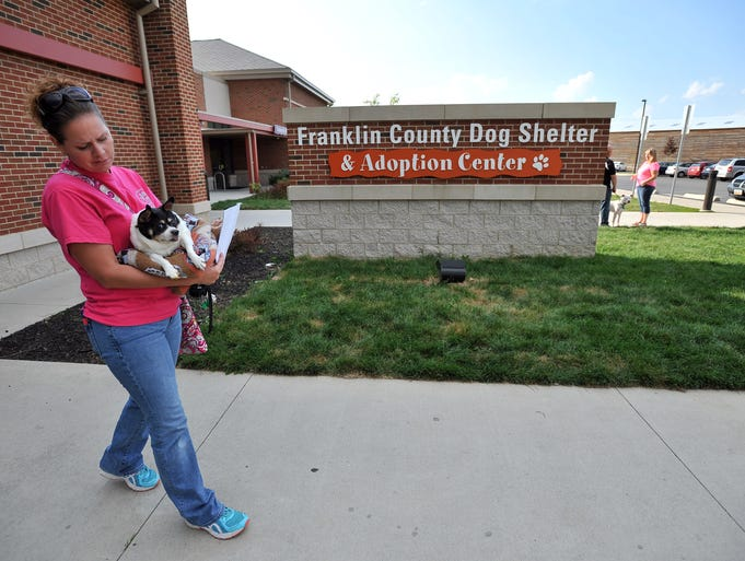 Tonya Walls walks out of the Franklin County Dog Shelter and Adoption Center with Sunny a dog she and her Tuff Rescue cofounder Blue Jones pulled from the shelter Wednesday, Aug. 20, 2014, in Columbus.