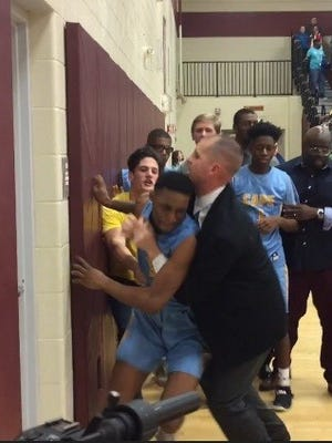 Cape Henlopen boys basketball coach Stephen Re (in dark suit) tries to restrain one of his players during a brawl that broke at Thursday night's game against Smyrna at Milford Central Academy.