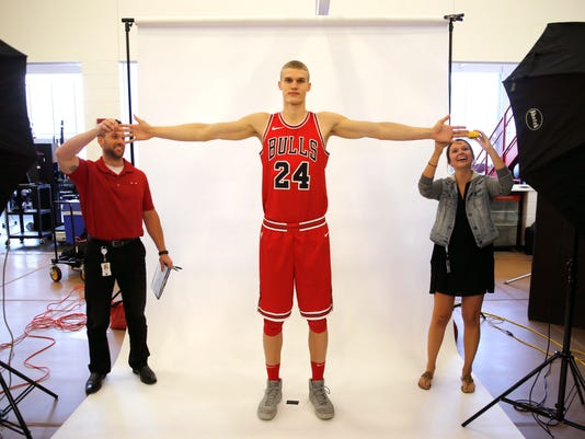 Dave Zarzynski, left and Katie Hanrahan, right, measure Chicago Bulls' Lauri Markkanen's wingspan during media day for the NBA basketball team Monday, Sept. 25, 2017, in Chicago. (AP Photo/Charles Rex Arbogast)