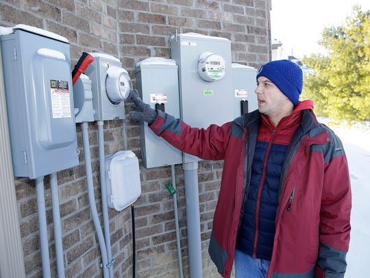 """The language in the HOA covenants for Joey Myles' Franklin Trace neighborhood was vague but allowed solar panels with committee approval, but the committee then kept denying his request for """"aesthetic"""" reasons. Here Myles explains the electrical and solar meter readers at his home on Wednesday, Jan. 17, 2018."""