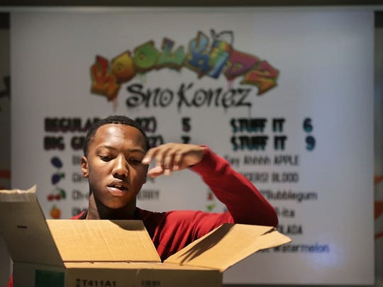 Jaden Wheeler helps set up the Kool Kidz Sno Konez booth inside the FedExForum Saturday afternoon with his sister in preparation for the first preseason game. The sibling team started a little front yard business on a card table with an extension cord and a blender when they were just 9 and 10 years old which has now grown into a stand at the Forum.