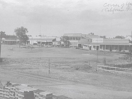 This circa 1890 image of Redding captures an intriguing view at the intersection of California & Yuba Streets. An open space is visible with a rocky waterway and several buildings in the background. The buildings belong to D. Breslauer, the Miller and Eaton Drug Store, the Paragon Hotel, and the City Drug Store. A lonely tree appears in the middle of a lot in and that lot is now the present site of the Lorenz Hotel. SHS 1950.189.1b