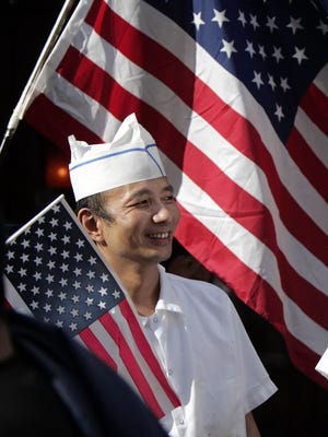 Chinese restaurant owner Vince Yong watches an immigration rally go to the Federal Building in downtown Seattle. Monday, April 10, 2006,