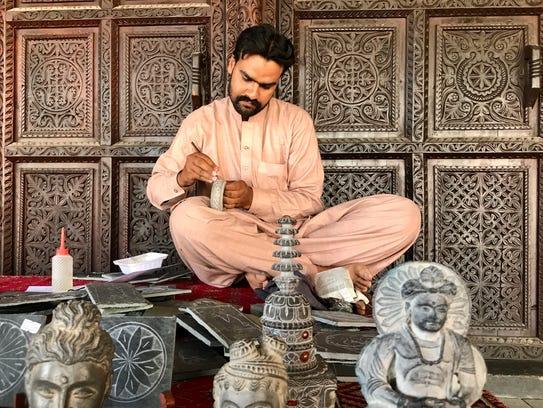 A Pakistani man carves a stone bowl outside of Lok