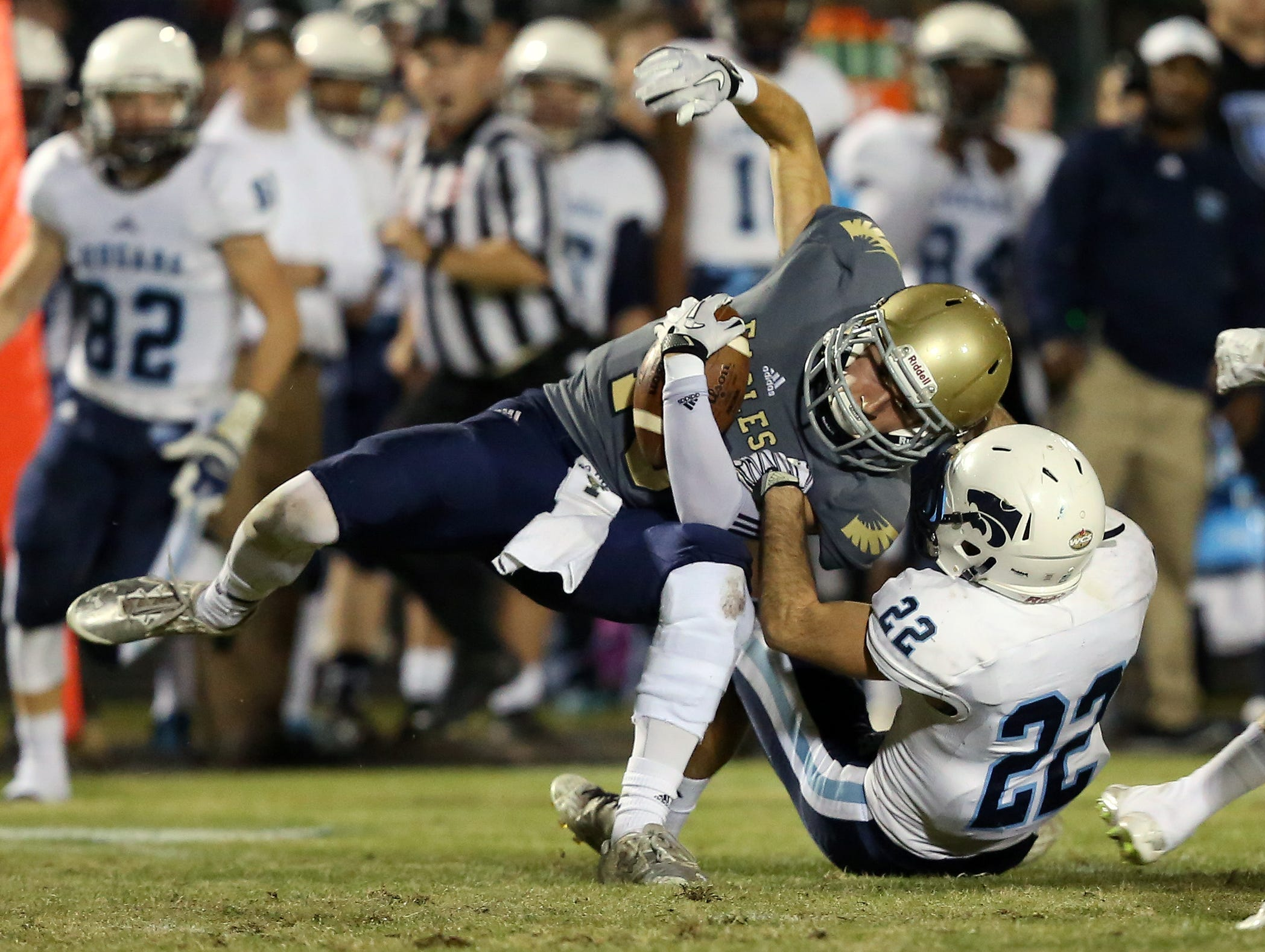 Independence's Nate Johnson is brought done by Centennial's Peyton Pisacane (22)