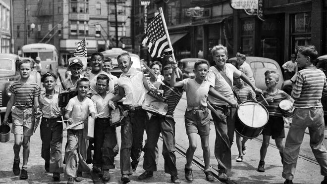 "On V-J Day -- Aug. 14, 1945 -- boys celebrate World War II's end on Main Street in Pawtucket. From left: David Sutton, Norman Thomas, Alfred Thomas, Donald Freda, Norman Tavares, John Sadlier, Donald O'Gara, Jim Welch, Bob ""Red"" Luther, Joe McCabe, George ""Buddy"" Young, Phil Moran, Paul Sutton and Jack ""Cy"" Welch."