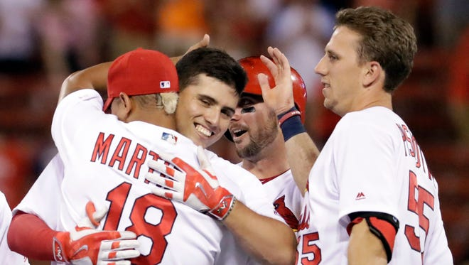 St. Louis Cardinals' Aledmys Diaz is congratulated by teammates Carlos Martinez (18) and Stephen Piscotty, right, after hitting a walk-off single during the ninth inning of a baseball game against the San Diego Padres Thursday, July 21, 2016, in St. Louis. The Cardinals won 6-5.