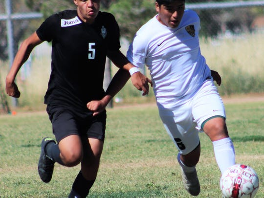 Alamogordo's Jr. Barbosa, right, dribbles a ball down field while being defended by Santa Teresa's Andrew Morales.
