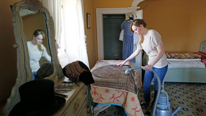 Curatorial technician Natalie Zaremba vacuums a linen through a screen in a guest room at Washington Irving's Sunnyside home, March 21, 2014.